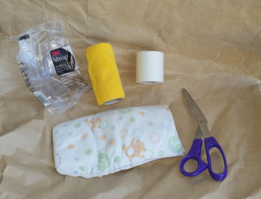 Vet wrap, paper tape, a disposable diaper and a pair of scissors will do the trick.