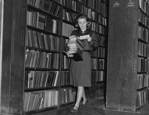 "This librarian, working in 1964, is checking ""due"" dates of her books"