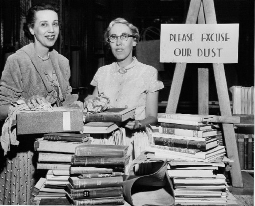 Two librarians in the 1950s sort through a supply of books to see which ones are suitable for including them in their library