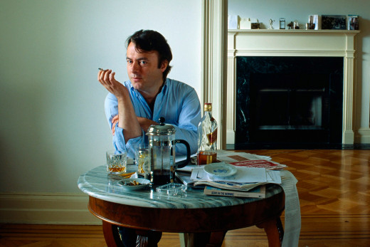 Hitchens at his Washington, DC home with trademark cigarette and whisky (but red label rather than the famous black).