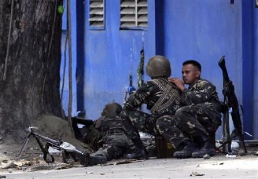 An army sniper aims his rifle at Moro National Liberation Front snipers from behind a tree in Zamboanga, where security forces are battling hundreds of rebels who are holding dozens of civilian hostages.