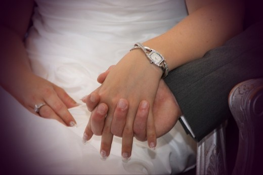 male and female hands clasped together with a white wedding gown