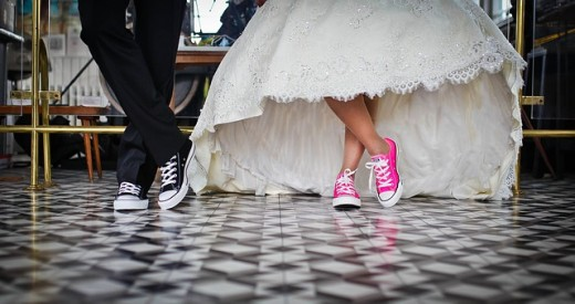 fun wedding with pink sneakers on the female with the white hooped gown and black sneakers on the gent!