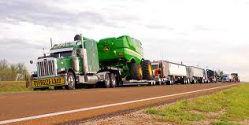 Two huge trucks deliver an upgraded John Deere wheat combine