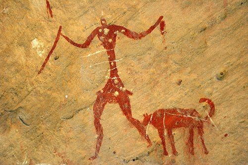 A prehistoric painting showing a human with a dog like animal.