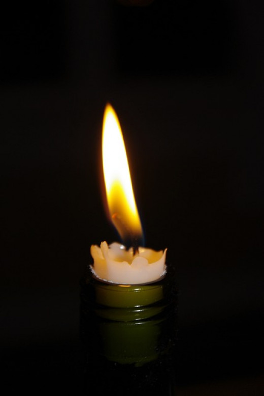 This is a taper candle burning in the mouth of a bottle. Alternatively, place a votive or pillar candle on the cap of a closed jar. Each time you burn a candle, let the wax accumulate and remain on the jar.