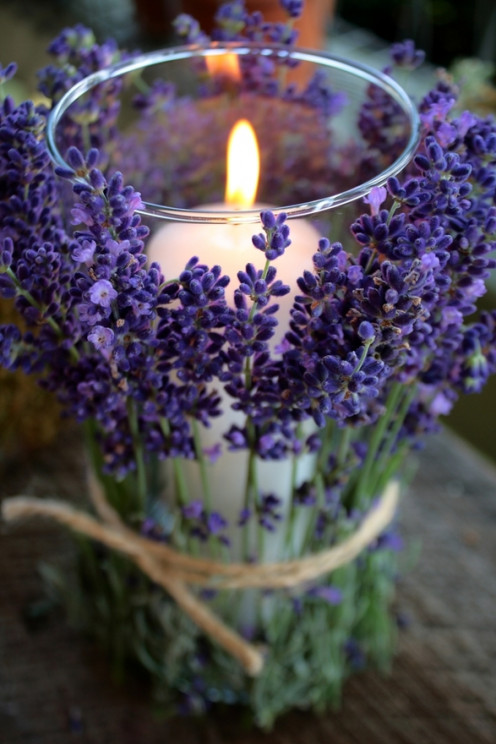Lavender sprigs tied with twine around a clear glass candle holder.
