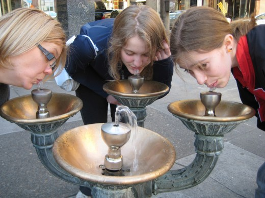 three people drinking from water fountain
