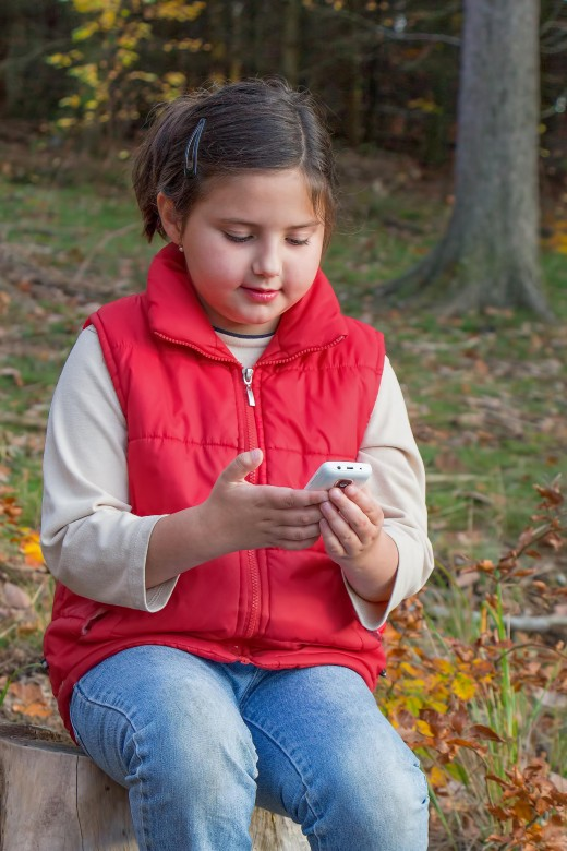 young girl in red vest viewing her cell phone