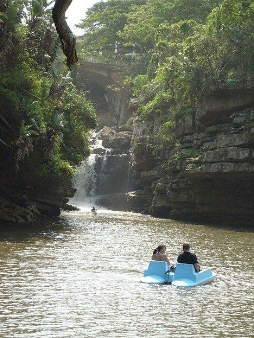 beautiful water way with cliffs on each side with a blue pedal boat with two people