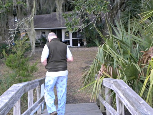 My husband relaxing and goofing off before heading to work....he's drinking his coffee and walking on the dock.