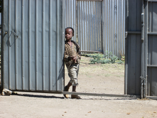Dawit Dereje - standing outside the school's gate - before he was enrolled.