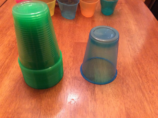 Stack of green and one blue cup