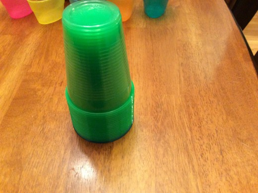 Green cups stacked on top of blue cup
