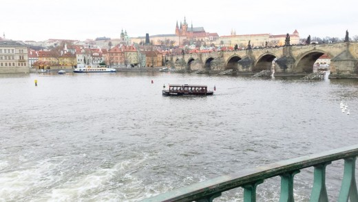 Karlův most, with the Vltava River in the foreground and Prague Castle in the distance. The bridge has been damaged repeatedly by floods during its 600-plus year life, but is today Prague's most accessible tourist attraction.