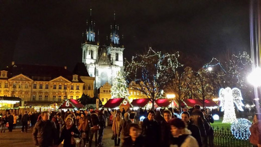 Crowds of thirtysomethings enjoy the bracing holiday ambiance of the Old Town square at night.