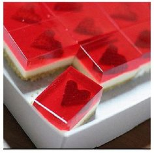 Strawberry jello with heart-shaped slice of strawberry.