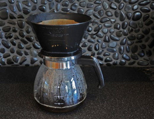 A simple cone coffee filter on a glass coffee pot.