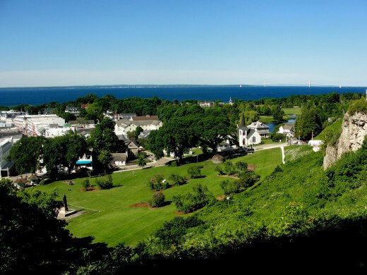 An overview of the downtown area of Mackinac Island.  In the background is Lake Huron, mainland Lower Peninsula, and the Mackinac Bridge.