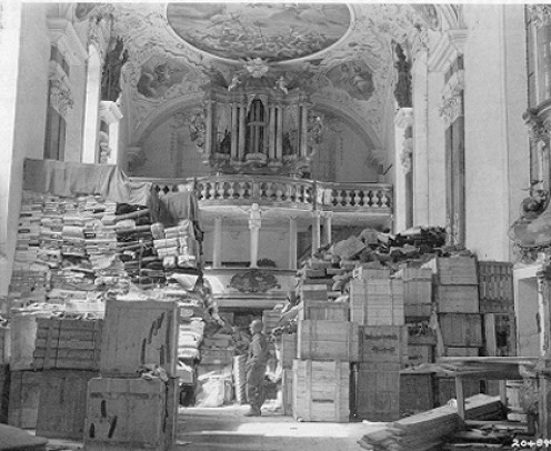 American soldier inspects German loot stored in a church at Elligen, Germany, April 24, 1945