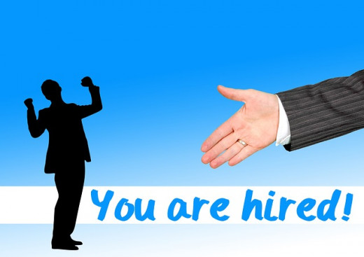 You Are Hired colorful sign with handshake and silhouette cheering