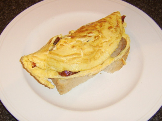 Omelette is carefully laid on first slice of bread