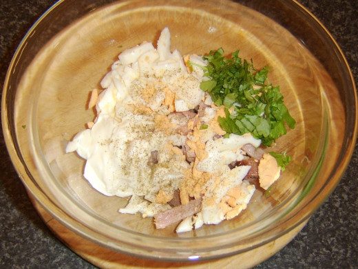 Sausage, bacon and egg added to bowl with mayo and parsley