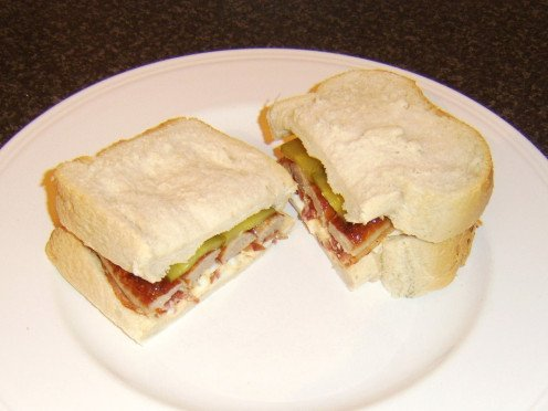 Bacon, egg and sausage sandwich is enhanced with a couple of pickles