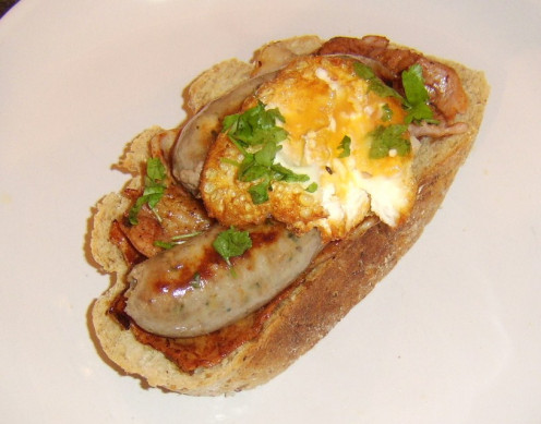 Bacon and sausage are topped with a poached and deep fried egg in an open sandwich