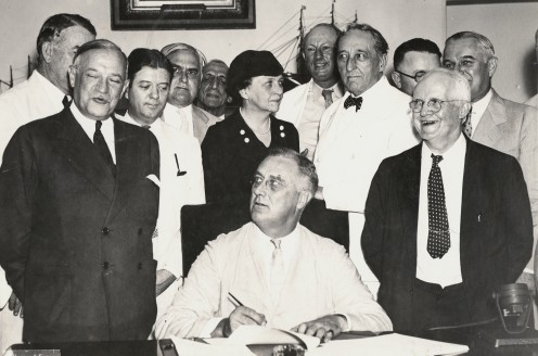 President Roosevelt signing the Social Security Act. Among those with the President are Senator Alben Barkley, Senator Robert Wagner, Senator Robert LaFollette, Secretary of Labor Frances Perkins, Representative Pat Harrison, and Representative David
