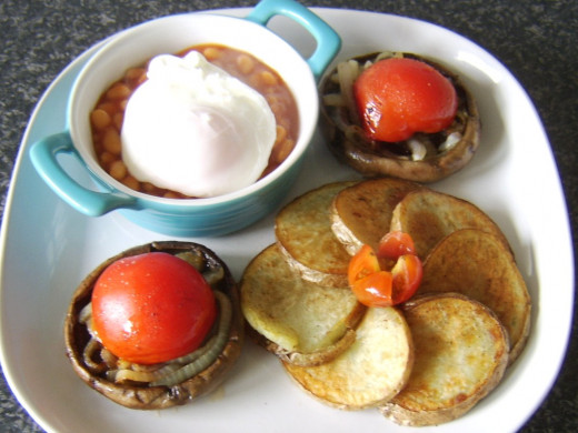 Poached egg is laid on beans and small cherry tomato on potatoes
