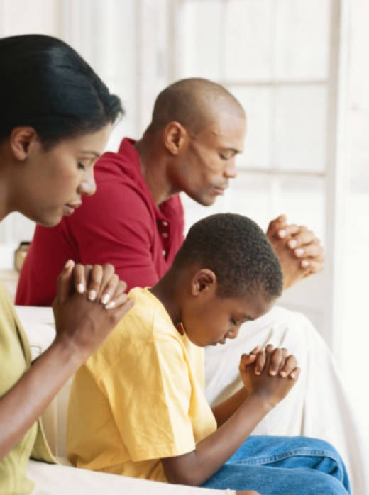 Parents praying with their only child.