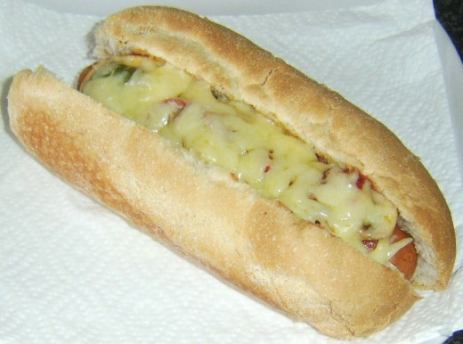 Tomato sauce, mushrooms, peppers and melted cheese on a hot dog
