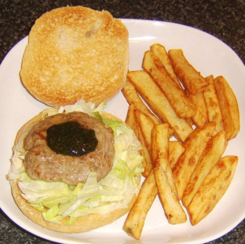 Lamb burger on a lettuce bed on a bread roll with mint sauce and served with homemade chips