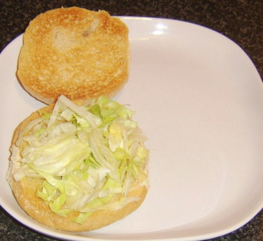 Shredded iceberg lettuce is laid on bottom half of toasted roll