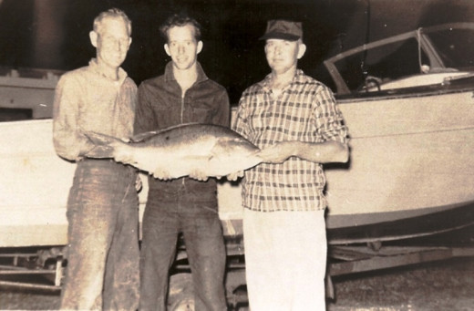 After a day in the Everglades, the fishermen display this prized Redfish. Standing at the head of the fish is my Dad with two men from The Herald.