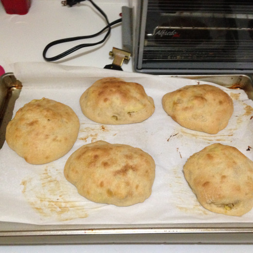 Finished breakfast pockets cooling on a cookie sheet.