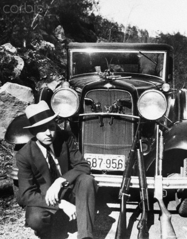 Clyde Barrow, half of the robbery-team of Bonnie and Clyde, poses with guns and fancy auto.