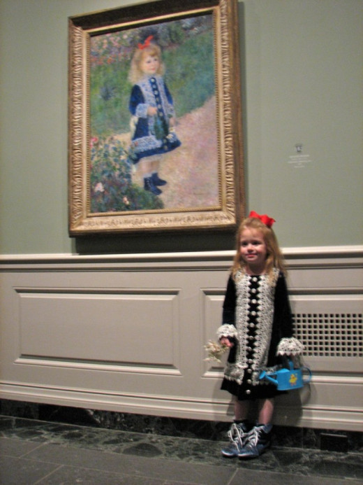 famous Renoir painting of the little girl in blue with the watering can with a real child dressed in a similar fashion in front of the artwork