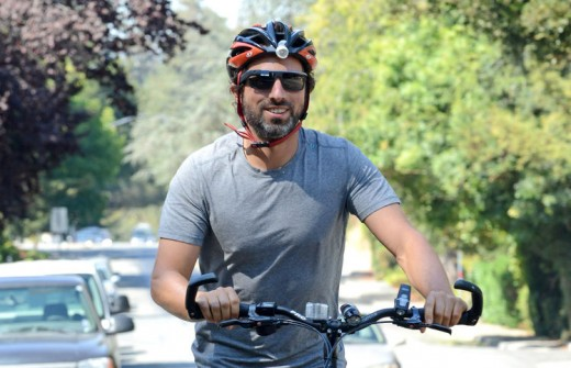 Sergey Brin on a bicycle with a safety helmet on