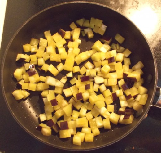Diced eggplant cooks in oil in a small frying pan.