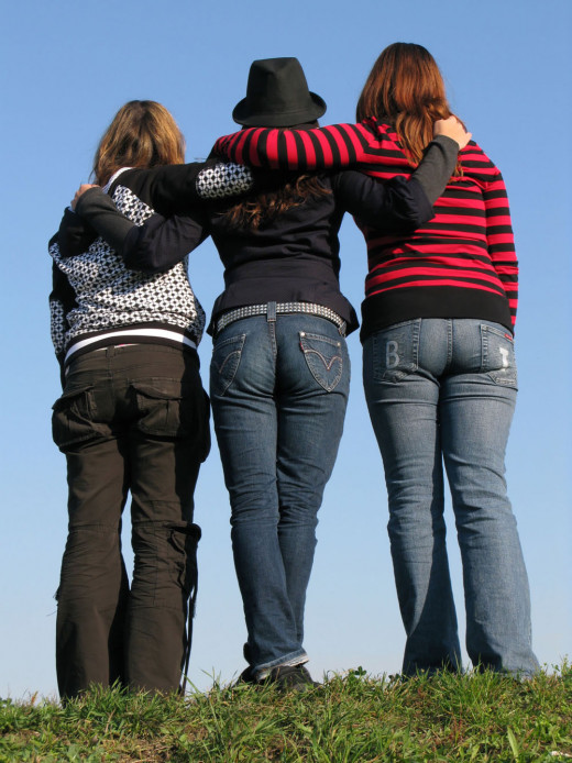 Three young women with their arms over each other's shoulders.