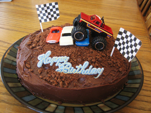 Chocolate (mud) cake with toy monster truck and cars used as cake toppers. The checkered flag cupcake picks are great addition too.
