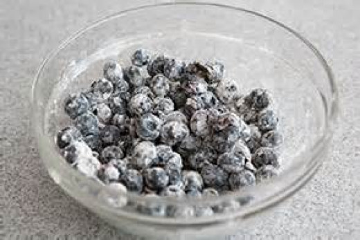 Mix blueberries in flour