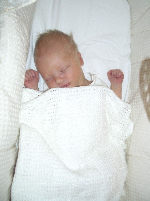 A newborn baby (my son) in a cot in an National Health Service hospital maternity and neo-natal ward