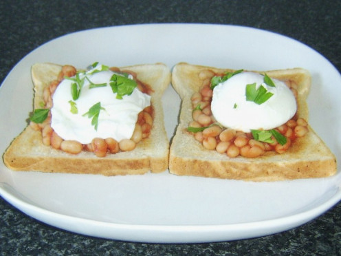 Haricot beans in homemade tomato sauce on toast with poached eggs