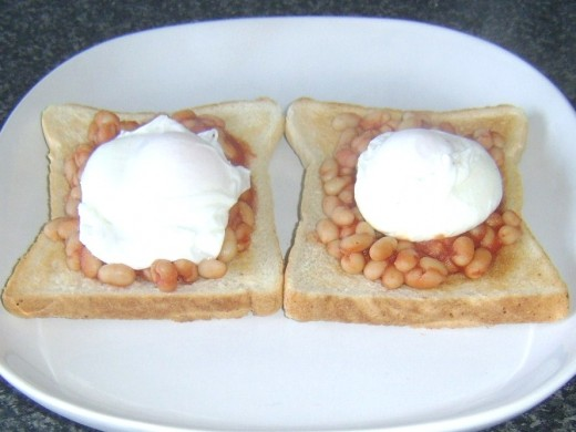 Poached eggs laid on spicy beans in tomato sauce on toast