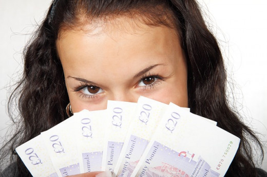 Personal Finance - woman with brown eyes hair holding bank notes covering her nose and mouth