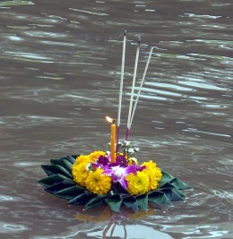 A lit  krathong floating down the Ping River in North Thailand