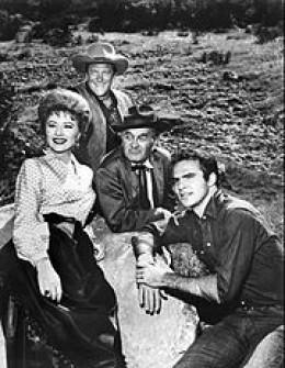 "A pre-Ken ""Festus"" Curtis photo of cast of Gunsmoke: Amanda Blake, ""Kitty,"" Burt ""Quint Asper"" Reynolds, James ""Matt Dillon"" Arness and Milburn ""Doc"" Stone."
